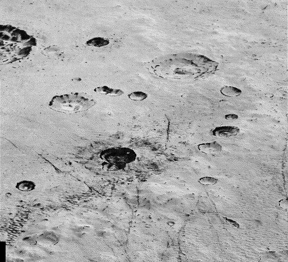 """Cratères d'impacts nombreux (surface très âgée) montrant des """"terrasses"""" internes révélant un litage, une """"stratification"""" des premiers kilomètres superficiels de la croute de glaces de Pluton"""