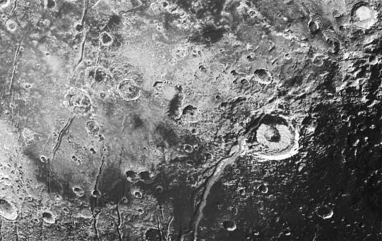 Réseau de failles normales et de graben recoupant de nombreux cratères d'impact plutoniens, dont le cratère Elliot au centre droit de l'image