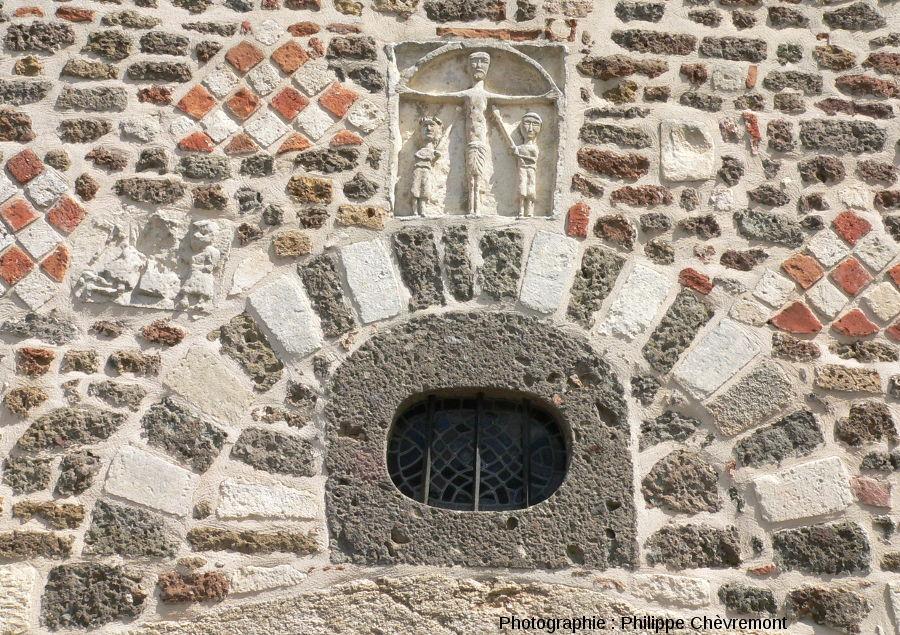 Au-dessus de l'entrée de l'église de Chassenon, originale et harmonieuse association de brèches de retombée, de calcaires et de briques