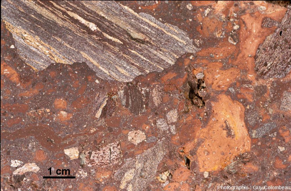 Une brèche de Montoume, ici à nuances rosâtres, à clastes de gneiss et de (micro)granite et riche en verre