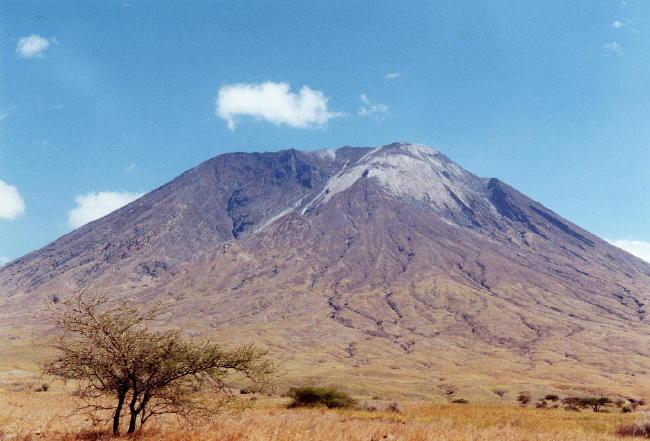 Photographie du volcan Oldoinyo Lengaï, prise depuis le sol de la vallée du rift Est-africain