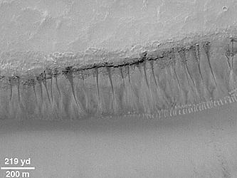 Exemples de ravines s'initiant à partir d'une couche spécifique située à environ 100 m de la surface de Mars