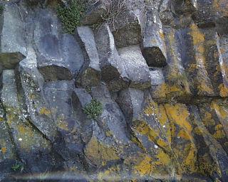 Gros plan sur les prismes basaltiques de la coulée observable sous la tour de Mirabel