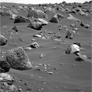Un champ de roches vacuolaires partiellement recouvert de sable