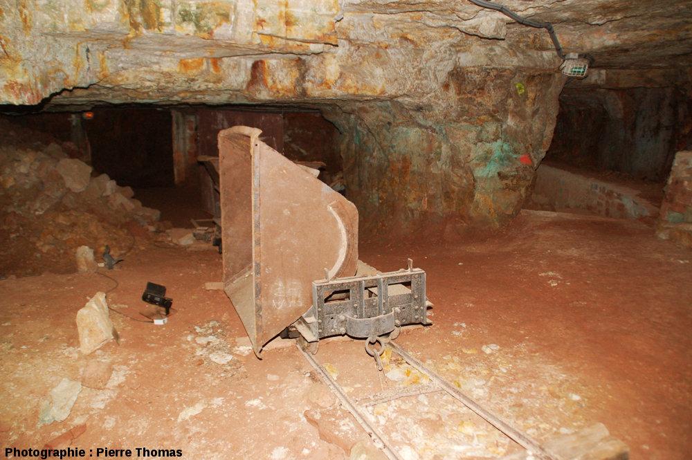 Une salle, avec un pilier et des restes de l'équipement d'exploitation (rails et wagon)
