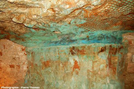Vue d'ensemble d'un pilier montrant un niveau de grès à stratifications obliques soulignées par diverses teintes de bleus dues aux sels de cuivre