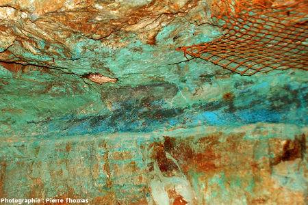 Vue de détail d'un pilier montrant un niveau de grès à stratifications obliques soulignées par diverses teintes de bleus dues aux sels de cuivre