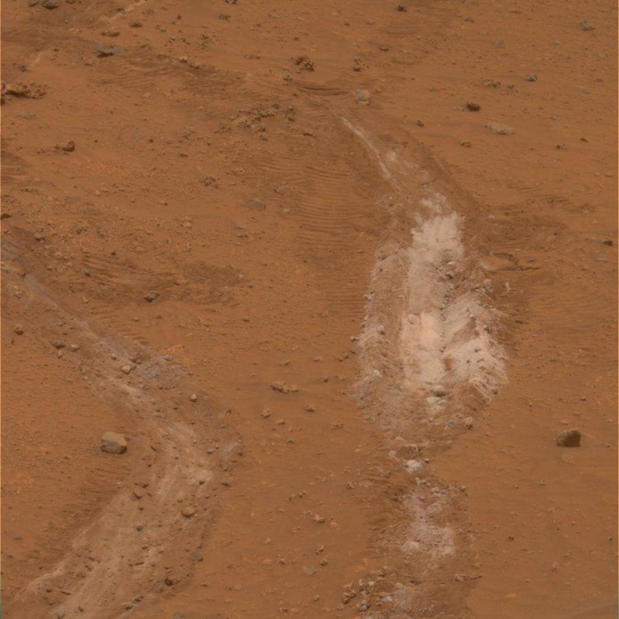 Mars: tranchée creusée (volontairement) par une des roues de Spirit laissant apparaître une substance blanche sous la couche superficielle de poussières rougeâtres