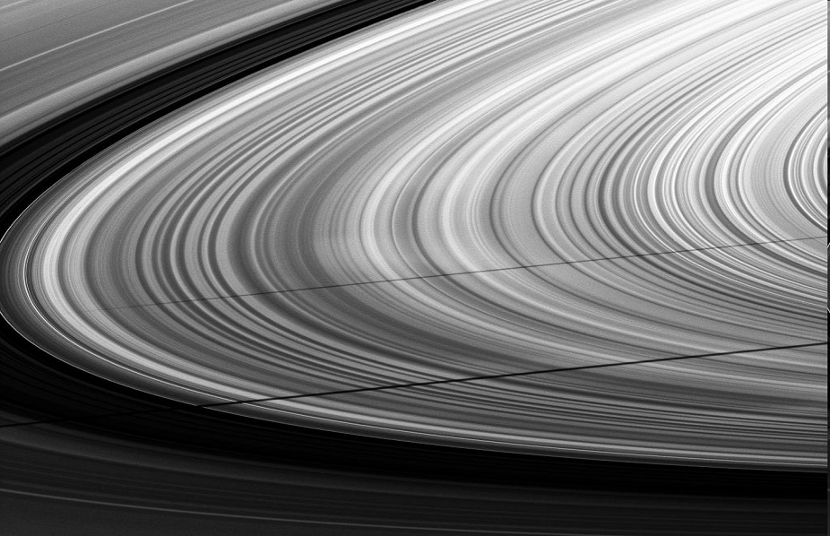 Les anneaux de Saturne rayés par les ombres de deux satellites, Mimas (en bas) et Janus (au centre)