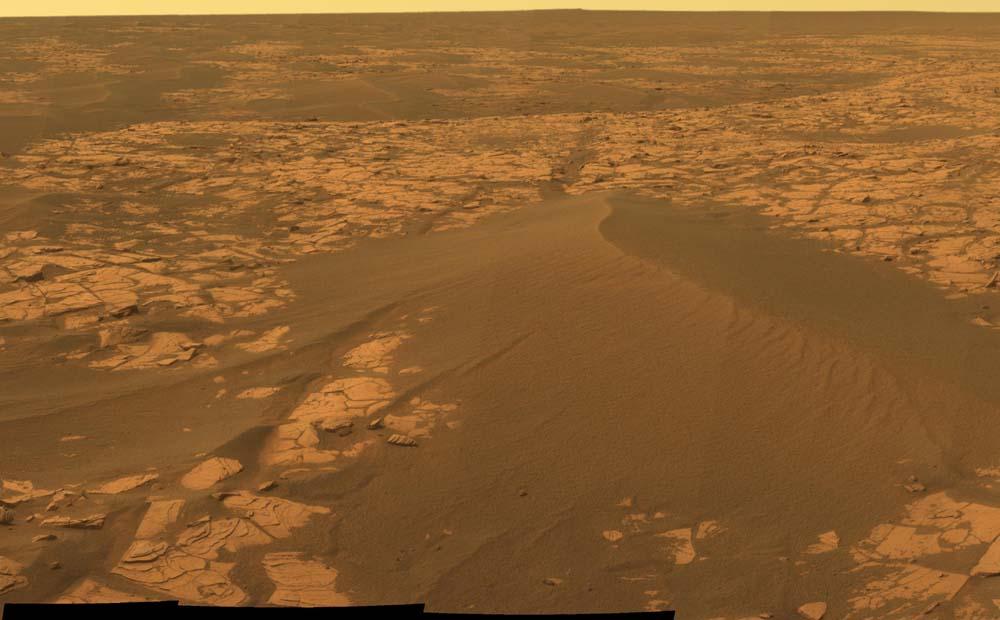 Détail d'une dune et de son substratum stratifié visible au premier plan à gauche de la dune