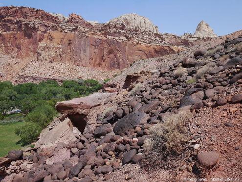 Rochers noirs (black boulders) d'andésites et basaltes formant un tablier d'éboulis bien développé dans les pentes qui surplombent l'oasis de Fruita (en bas à gauche de la photographie), au cœur du Parc national de Capitol Reef (Utah, États-Unis d'Amérique)