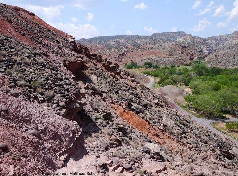 Rochers noirs (black boulders) volcaniques, mêlés à des blocs plus anguleux de grès rouges divers (formation Wingate notamment), formant un tablier d'éboulis bien développé au premier plan, dans les pentes qui surplombent l'oasis de Fruita (visible en bas à droite de la photographie), au cœur du Parc national de Capitol Reef