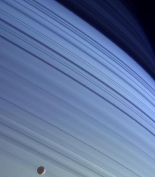"""Mimas devant le globe de Saturne, """"rayé"""" par l'ombre des anneaux"""