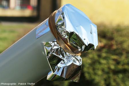 Filtre AstrosolarTM fixé à l'aide d'un élastique devant l'ouverture frontale d'une lunette astronomique de 63mm d'ouverture